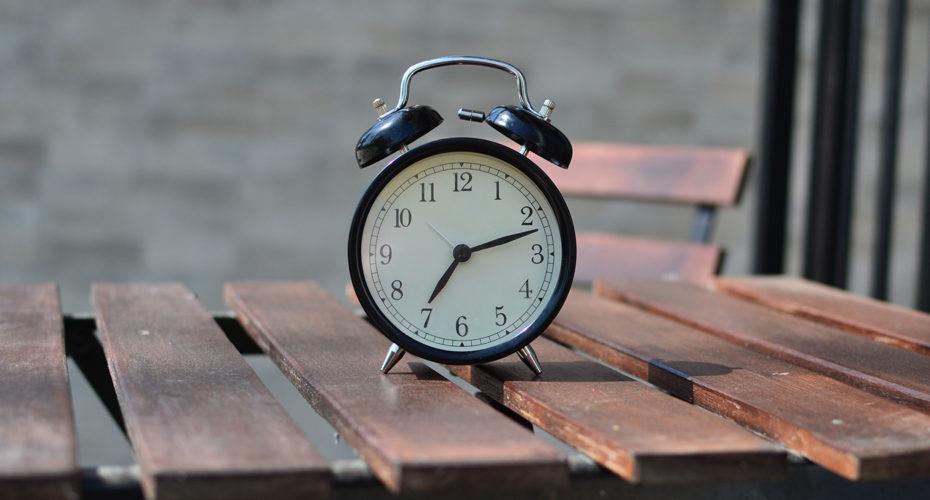 Der Unterschied zwischen wenn und als: Eine Uhr auf einem Holztisch